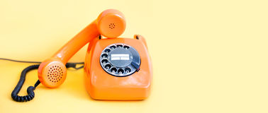 stock image of  vintage phone busy handset receiver on yellow background. retro style orange telephone communication call center concept