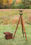 stock image of  vintage surveyors level (transit, theodolite) with wooden tripod and case in a field.