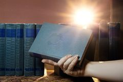 stock image of  female hand is holding a book, takes one book on the shelf. light of knowledge. the pursuit of knowledge