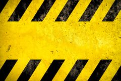 stock image of  warning background danger caution yellow black stripes painted over yellow concrete wall texture empty space text message