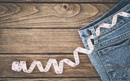 stock image of  weight loss concept, blue jeans and measuring tape on wooden background, top view with copy space
