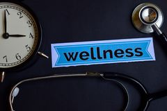 stock image of  wellness on the print paper with healthcare concept inspiration. alarm clock, black stethoscope.