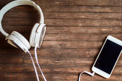 stock image of  white headphones and smartphone on timber background. hipster devices for music listening or entertainment.