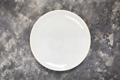 stock image of  a white plate. an object. clean. for food. view from above. for your design. texture.