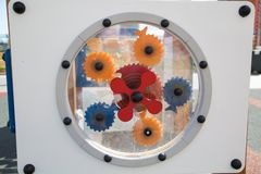 stock image of  white shield with plastic gears yellow blue red for the development of children`s.  children sport hobbies