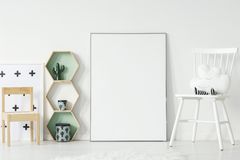 stock image of  white and wooden chair in kid`s room interior with mockup of emp