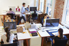 stock image of  wide angle view of busy design office with workers at desks