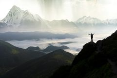 stock image of  wide mountain panorama. small silhouette of tourist with backpack on rocky mountain slope with raised hands over valley covered
