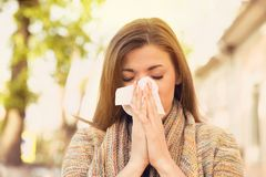 stock image of  woman with allergy symptoms blowing nose