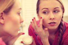 stock image of  woman applying moisturizing skin cream. skincare.