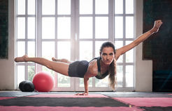 stock image of  woman balancing while doing a one hand push up showing strength
