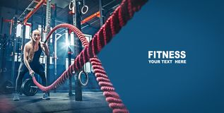 stock image of  woman with battle rope battle ropes exercise in the fitness gym.