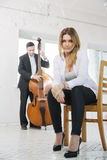 stock image of  woman on chair and man plays melody