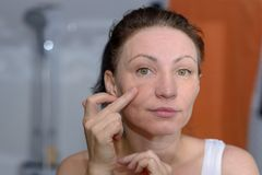 stock image of  woman checking her skin for signs of ageing