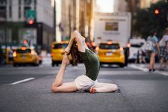stock image of  woman doing yoga pose on city street of new york.