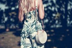stock image of  woman with fashionable stylish rattan bag and silk scarf outside. tropical island of bali, indonesia. rattan handbag and
