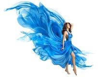 stock image of  woman flying blue dress, elegant fashion model fluttering gown