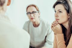 stock image of  woman listening to therapist during training for businesswoman in the office