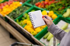 stock image of  woman with notebook in grocery store, closeup. shopping list on paper.