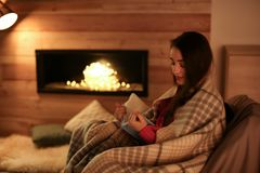 stock image of  woman reading book near decorative fireplace at home.