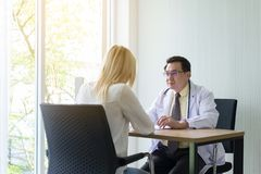 stock image of  woman talking to doctor psychiatrist in hospital,discuss issue and find solutions to mental health problems