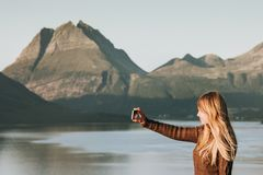 stock image of  woman tourist taking selfie by smartphone travel lifestyle concept adventure vacations outdoor norway sunset mountains and sea