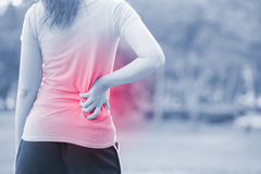 stock image of  woman waist injury in park