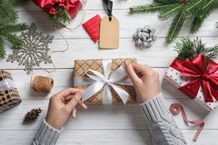 stock image of  woman wrapping christmas gift at wooden table