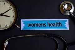 stock image of  womens health on the print paper with healthcare concept inspiration. alarm clock, black stethoscope.