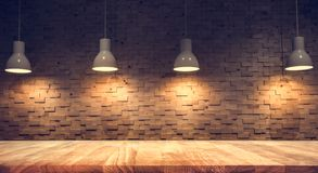 stock image of  wood table top on blurred of counter cafe shop with light bulb