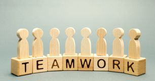 stock image of  wooden blocks with the word teamwork and business team of employees. the concept of cooperation. constructive feedback. joint