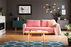 stock image of  wooden coffee table with tea cup and open book standing on carpet in dark living room interior with powder pink lounge with fur c