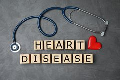 stock image of  wooden cubes with text heart disease and stethoscope on grey background