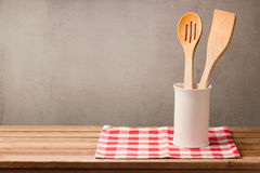 stock image of  wooden kitchen utensils on table with tablecloth over grunge wall background with copy space for product montage