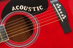 stock image of  word acoustic with wooden letters, closeup on a surface of red acoustic guitar. music entertainment background