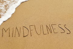 stock image of  word mindfulness in the sand