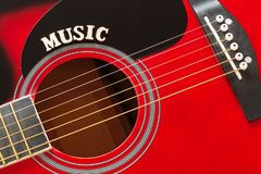 stock image of  word music with wooden letters, closeup on a surface of red acoustic guitar. music entertainment background