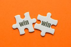 stock image of  the word win win on two matching puzzle on orange background