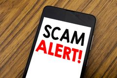 stock image of  word, writing handwriting scam alert. business concept for fraud warning written on mobile phone cellphone, wooden background with