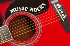 stock image of  words music rocks with wooden letters, closeup on a surface of red acoustic guitar. music entertainment background