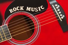stock image of  words rock music with wooden letters, closeup on a surface of red acoustic guitar. music entertainment background