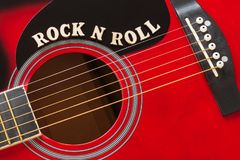 stock image of  words rock n roll with wooden letters, closeup on a surface of red acoustic guitar. music entertainment background