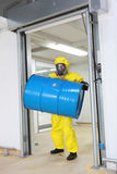 stock image of  worker lifting barrel of toxic substance