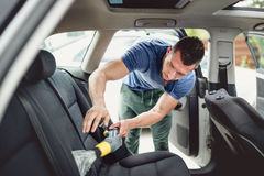 stock image of  worker vacuuming and cleaning automobile. car care and detailing concept