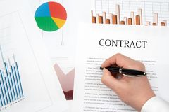 stock image of  workplace businessman. contracts, charts, and graphs on the desk