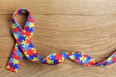 stock image of  world autism awareness and pride day or month with puzzle pattern ribbon on wooden background.