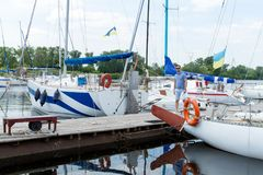 stock image of  yachtsman goes from boat on pier. young man moored his yacht in river dock. male hobbies and lifestyle.