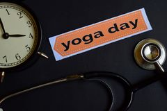 stock image of  yoga day on the print paper with healthcare concept inspiration. alarm clock, black stethoscope.