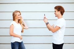 stock image of  young adult hipsters. boy and girl in white t-shirts smile and making selfie.