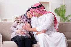 stock image of  the young arab muslim family with pregnant wife expecting baby